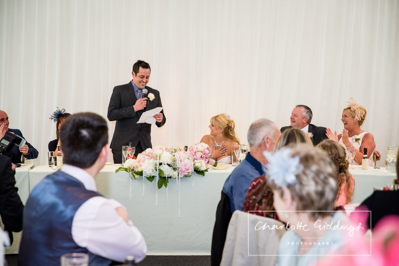 groom doing his speech at heaton house farm wedding venue with his bride feeling very touched