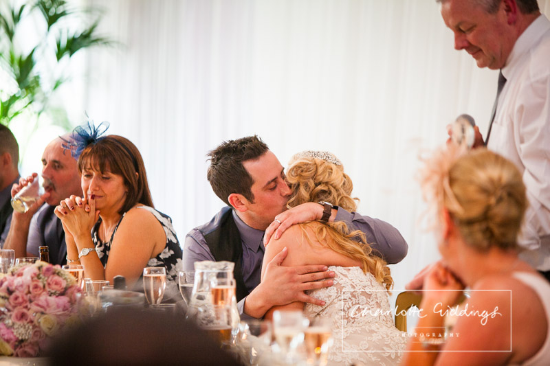 groom giving his bride a cuddle during the father of the bride speech - charlotte giddings photography