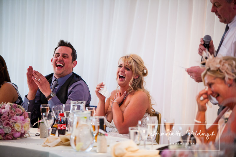 bride and groom and guests laughing out loud at father of the bride speech
