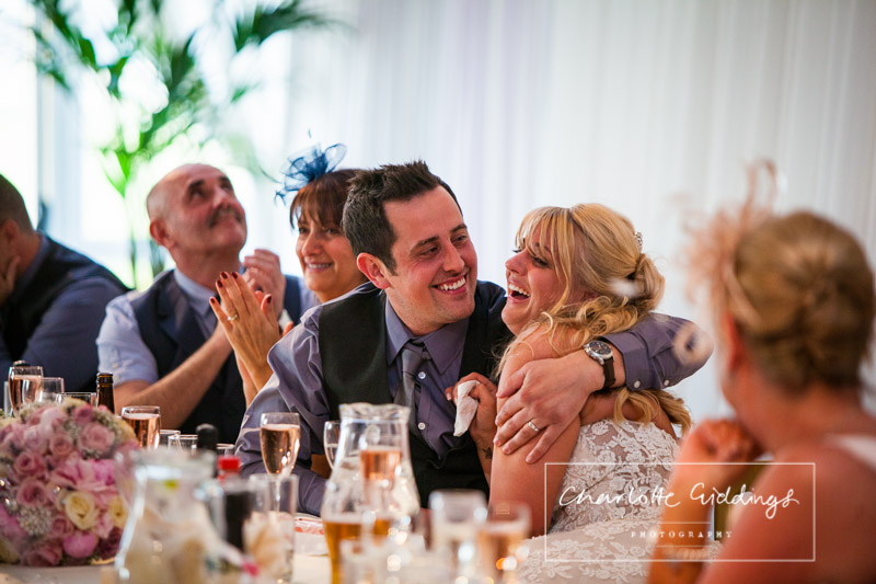groom looking and cuddling his bride adoringly as she laughs at the speeches