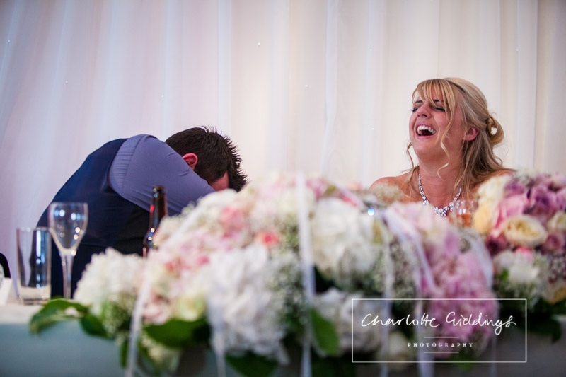 groom belly laughing at the best man speech and also the bride - shropshire wedding photographer