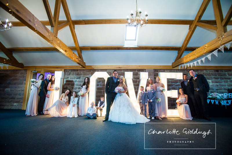 bridal party around love letters in heaton house farm wedding