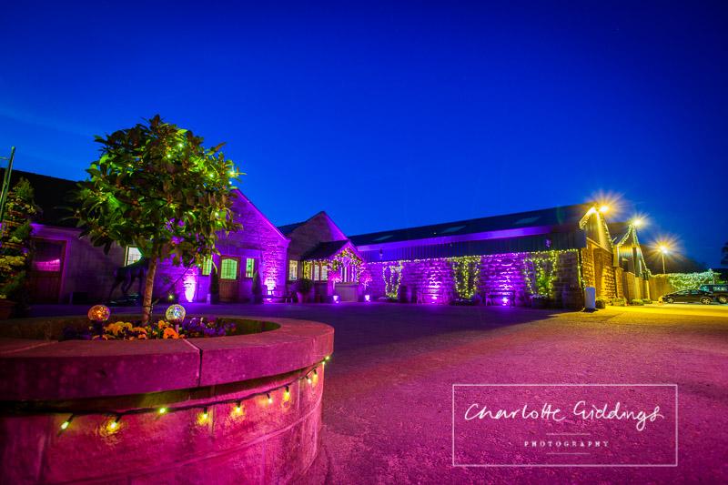 heaton house farm wedding venue lit up at night with fairy lights