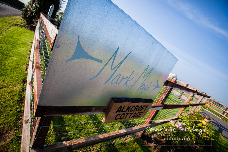 sign pointing to bride and grooms wedding hanging on the garden fencing - wedding photographer shropshire