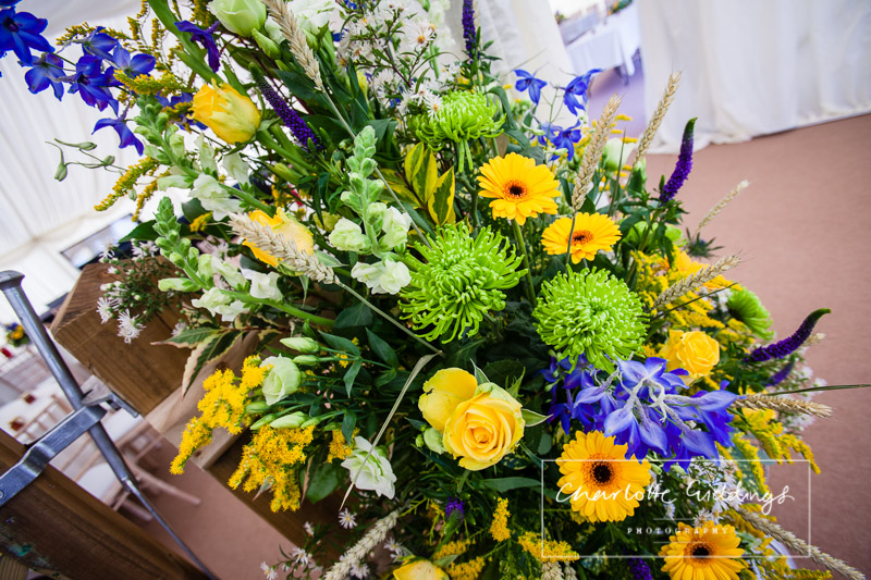 beautiful purple and yellow flowers in milk churns inside marquee - roses, irises, wheat