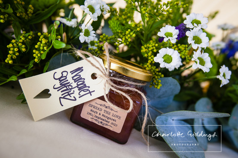 """""""spread the love"""" homemade jam made for guests for wedding favours along with wedding flowers"""