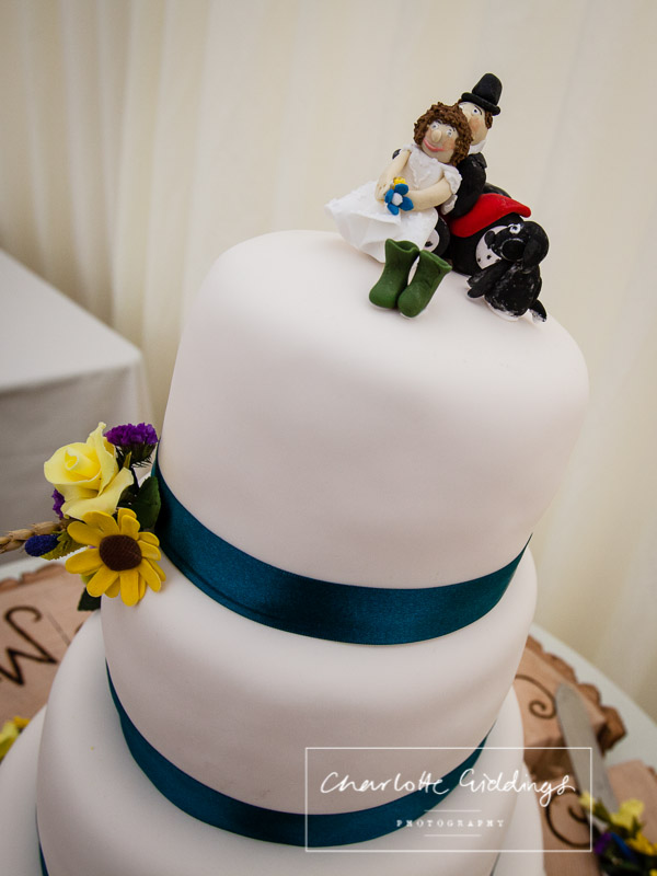 wedding cake consisting of wedding flowers, navy blue ribbon and iced figures with a dog