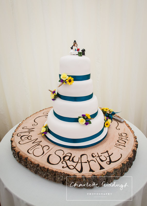 full wedding cake on personalised cake stand make of a tree cutting and bride and grooms etched in it