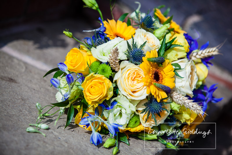brides homemade bouquet consisting of roses, thistles, wheat, irises