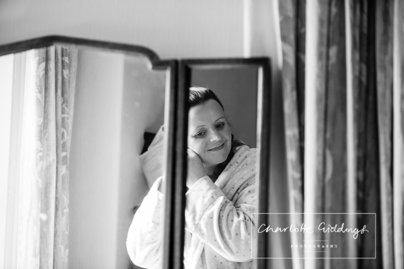 black and white photo of the brides reflection in the mirror looking down excited
