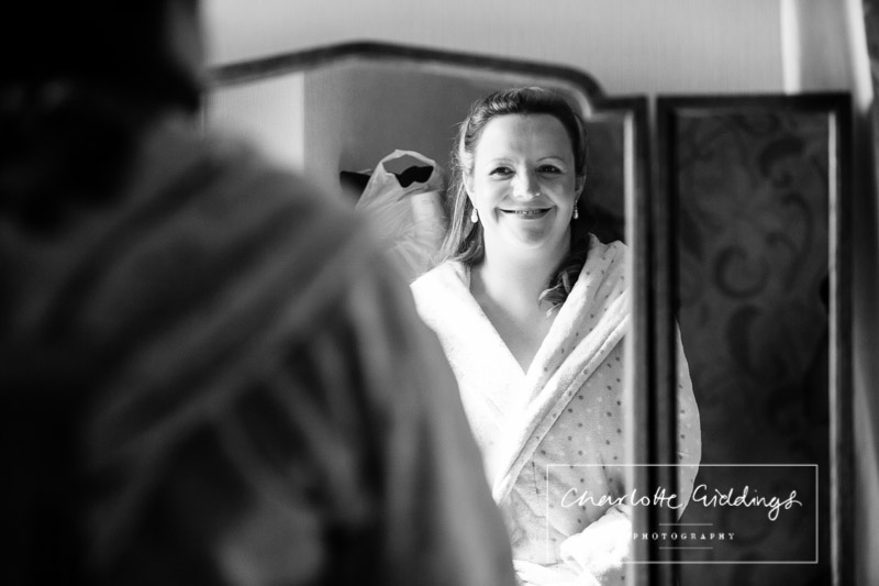 black and white photo of the bride smiling in the mirror- shropshire wedding photographer