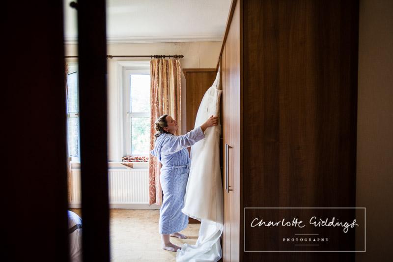 bride reaching up for wedding dress - shropshire wedding photographer