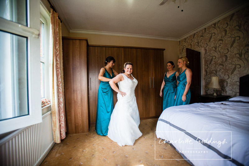 bride getting in her dress with her bridesmaids whitchurch shropshire wedding