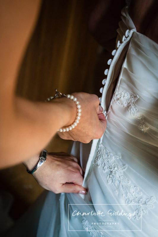 bridesmaid zipping up wedding dress for the bride
