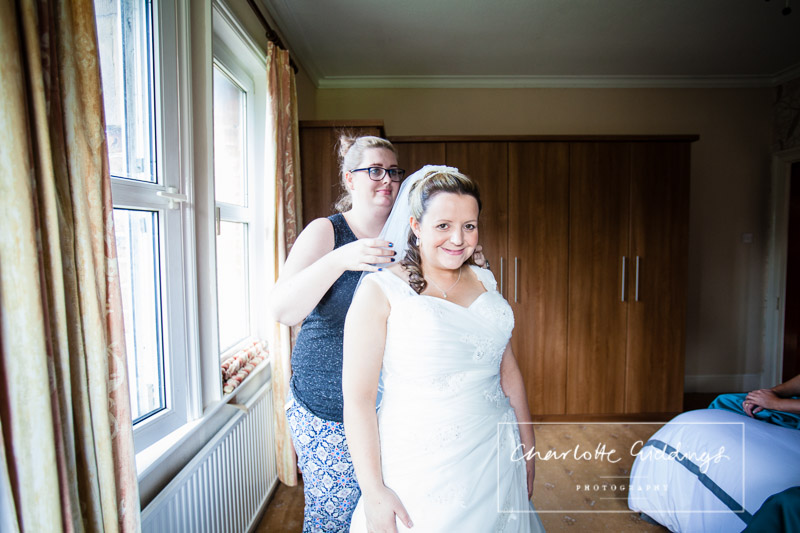 hair and makeup artist putting in brides veil at home -