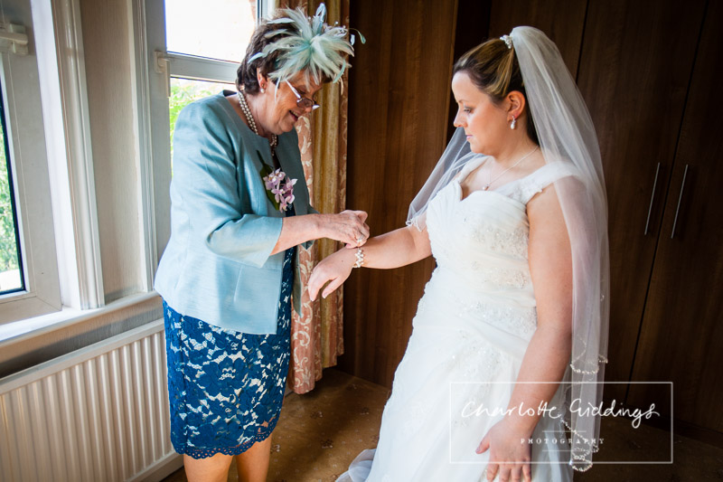 mother of the bride helping the bride put her wedding jewellery on - charlotte giddings photography