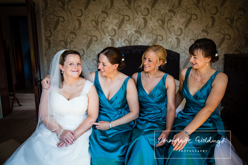 bride and bridesmaids giggling on the bed and looking at one another