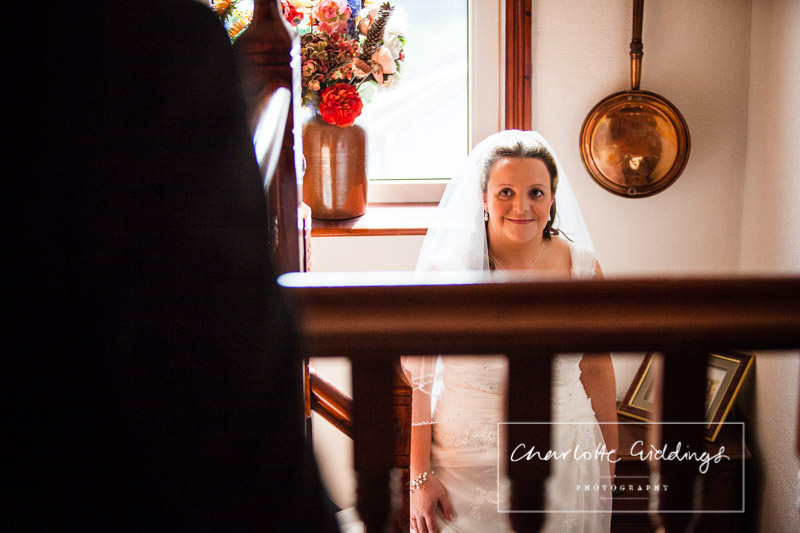 bride looking at her dad as she goes down the stairs in their shropshire farm home