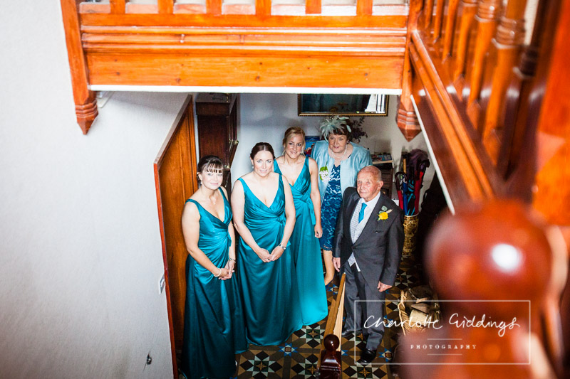 bridesmaids, mother of the bride and father of the bride looking at the bride as she comes down the stairs