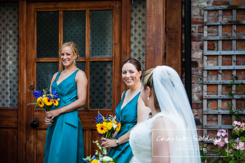 bride looking at her bridesmaids and them smiling back - shropshire wedding photographer