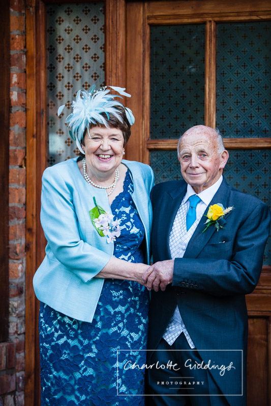 mother and father of the bride laughting together outside the family home - shropshire photographer