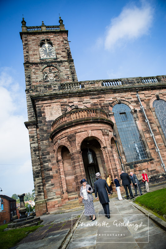 guests arriving at st. alkmunds church on a beautiful september day with blue sky