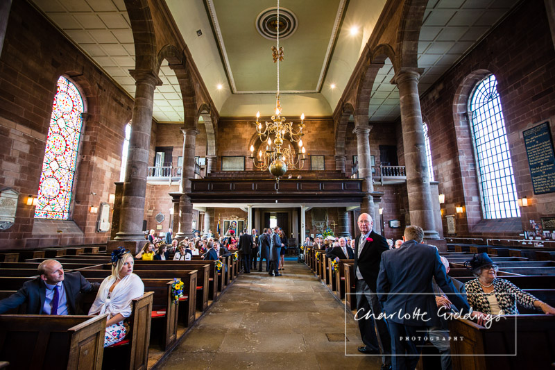 interior photo looking down the aisle while guests arrive at st. alkmunds church, whitchurch