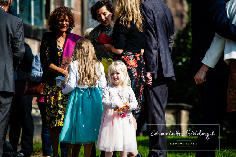guests arriving at st. alkmunds church and little girl looking back at the camera