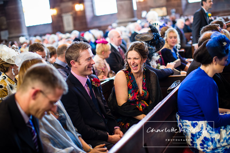 guests laughing while sat inside church, shropshire wedding photographer