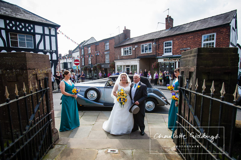 bride and father of the bride ready to walk up the path to church with wedding car from manor bridal in the background