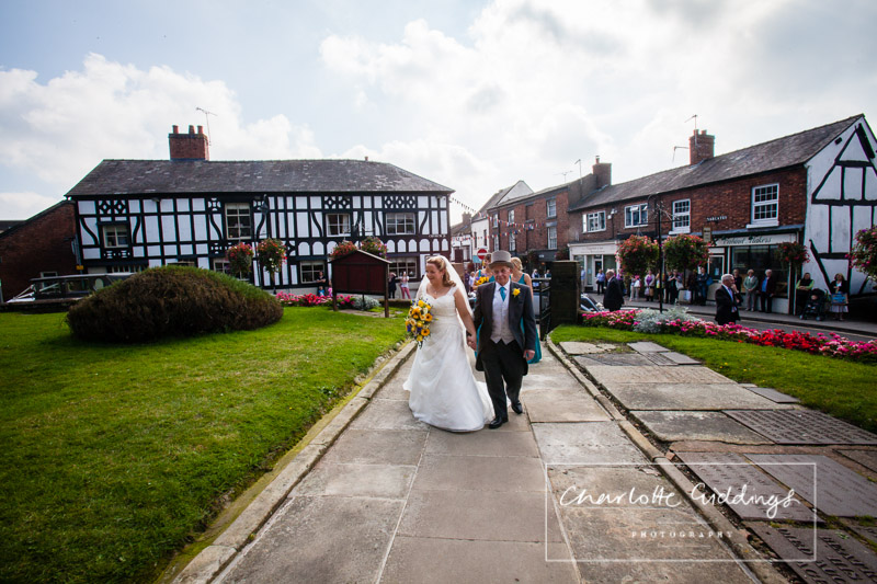 bride walking up the path of st.alkmunds church with her dad with whitchurch high street in the background