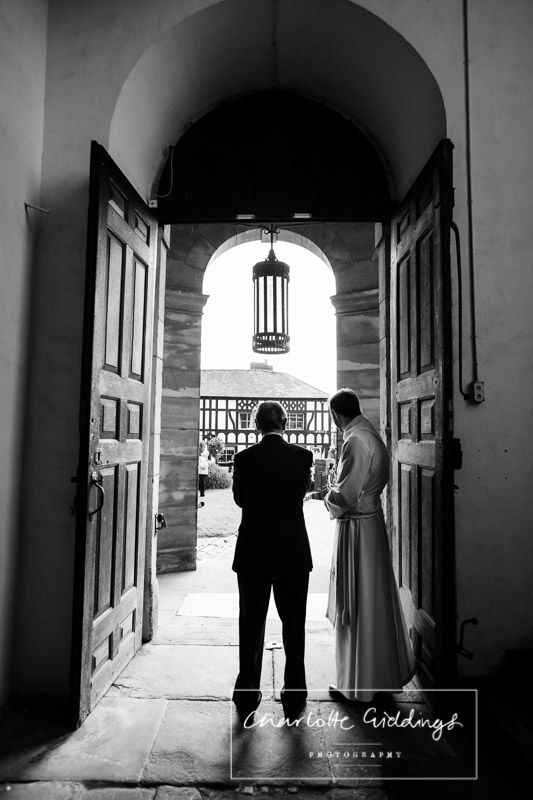 black and white photo of the vicar waiting at st.alkmunds church main doorway