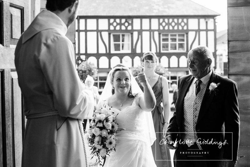 bride giving a friend the thumbs up as she arrives at the church doorway of st.alkmunds church whitchurch