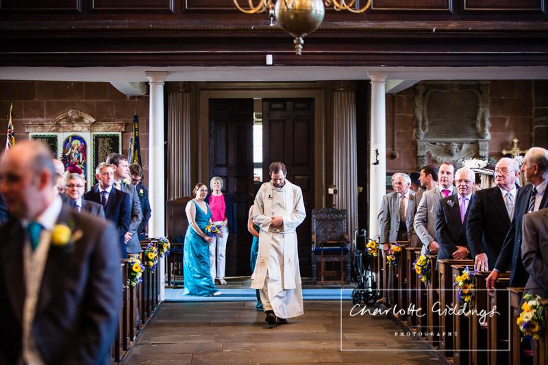 vicar walking up the aisle with bridesmaids starting to follow at shropshire wedding