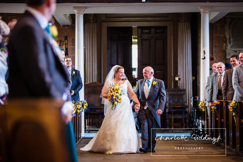bride and father of the bride looking at each other smiling as they walk down the aisle together towards the groom - shropshire wedding photographer