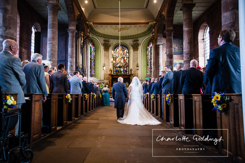 photo from the back of the church - back shot of the bride and father of the bride walking down the aisle and the stain glass window in the church