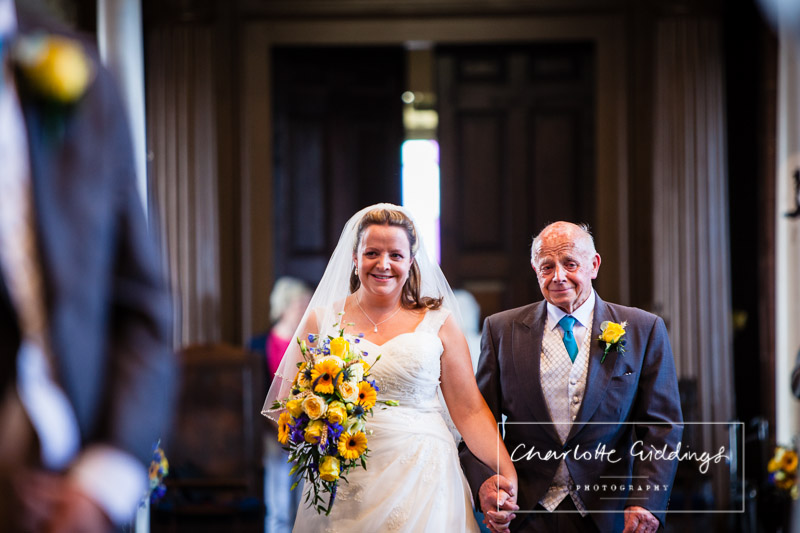 emotional bride and father of the bride walking down the aisle in st. alkmunds church