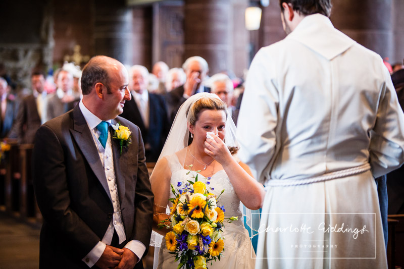 bride wiping away happy tears at the alter next to her husband - wedding photographer shropshire