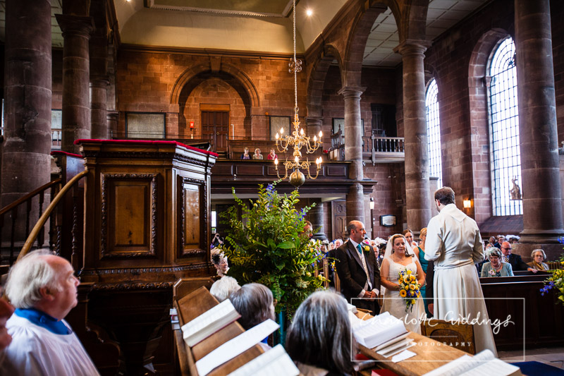 wide angle photo from the front of the church with the choir in the foreground and the bride and groom enjoying the ceremony