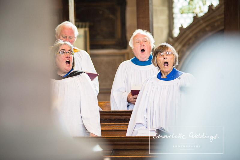 st alkmunds church choir singing a hymn in church - whitchurch shropshire wedding photographer