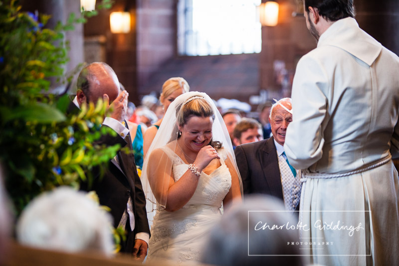 bride, groom and father of the bride giggling at a joke from the vicar - st. alkmunds church
