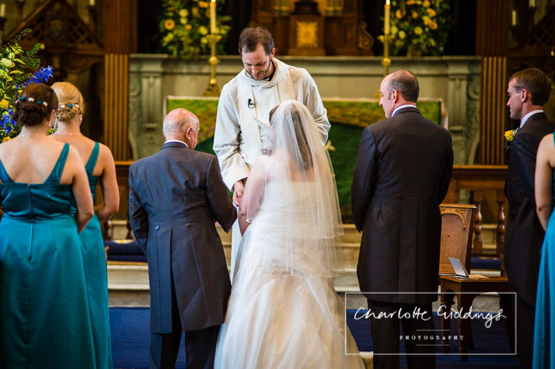 vicar assisting the father of the bride, giving away his daughter to the groom, shropshire wedding photographer