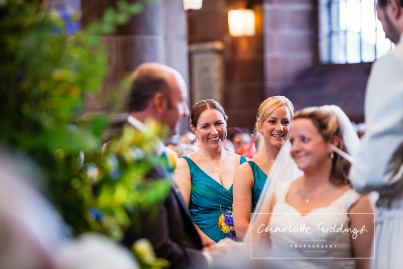 extremely happy bridesmaid looking at the bride and groom doing their vows - charlotte giddings photography