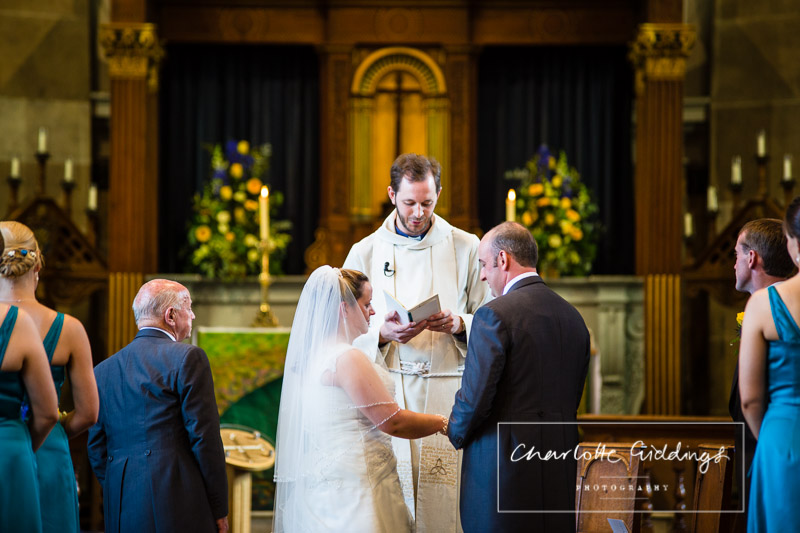 bride and groom saying their vows in church looking at one another- wedding photographer shropshire