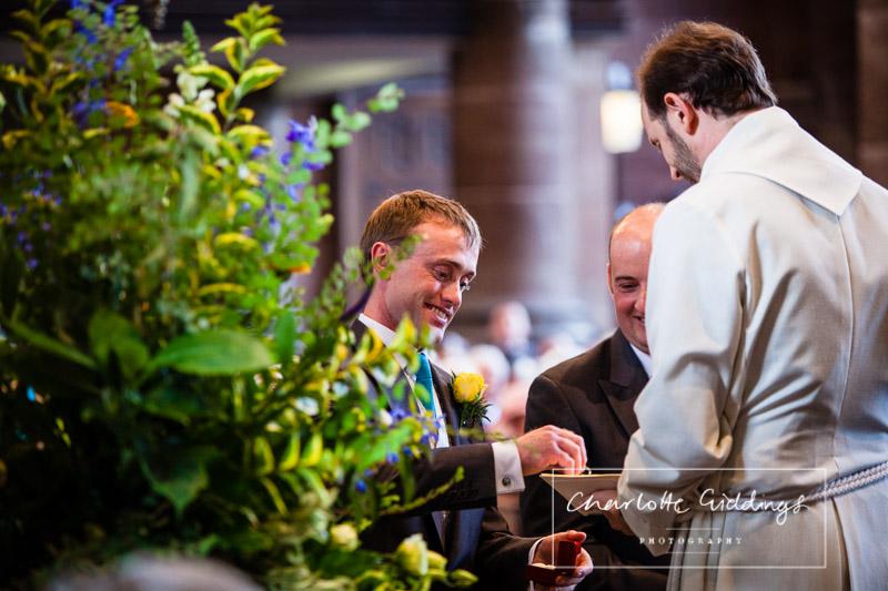 groom handing the rings over the vicar in st. alkmunds church
