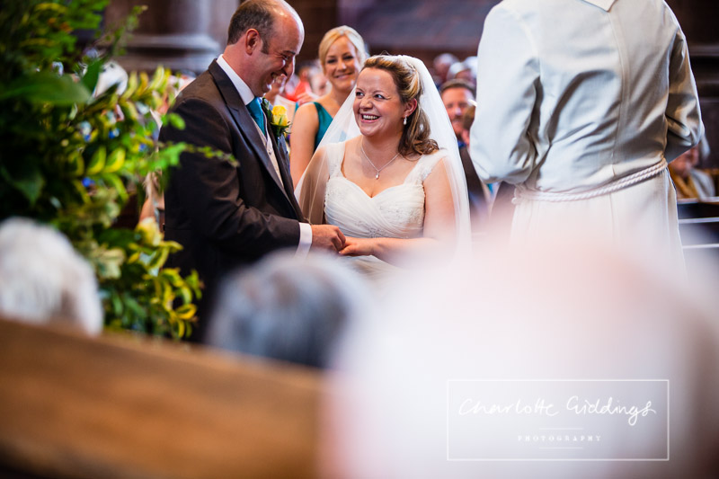 groom putting wedding ring on his brides finger while they have a giggle and looking at once another