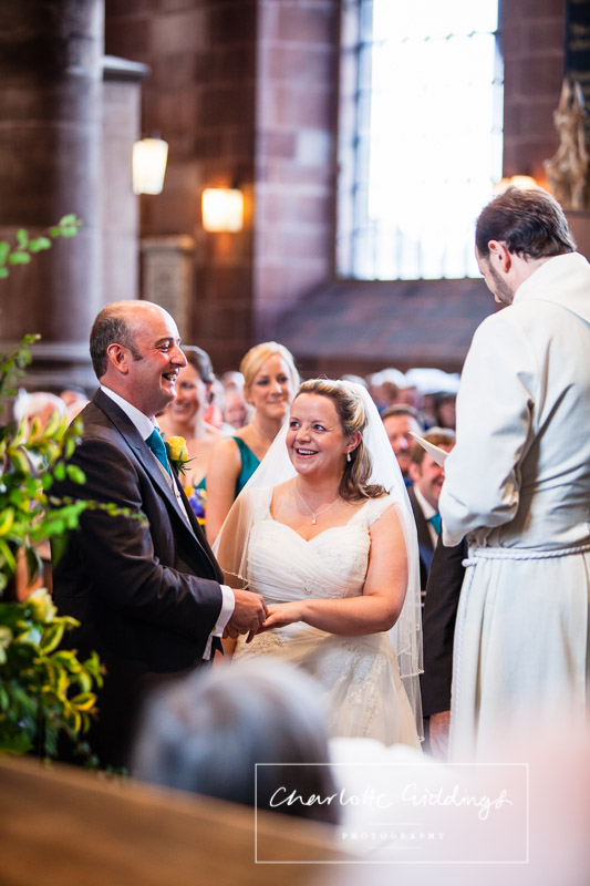 bride and groom laughing along with the vicar while exchanging rings