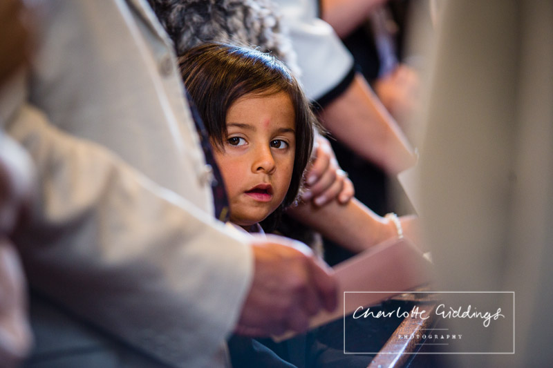 little boy looking at the camera while standing amongst the crowd singing a hymn - charlotte giddings photography