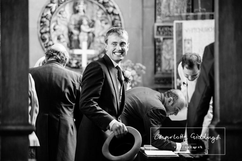 best man smiling back at the congregation in st. alkmunds church