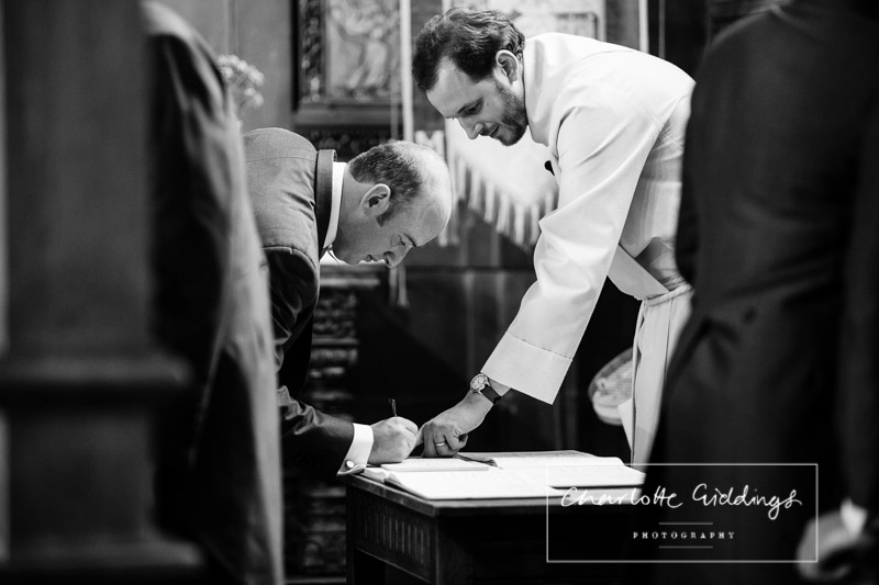 black and white photo of the vicar pointing to the registar and the groom signing the document